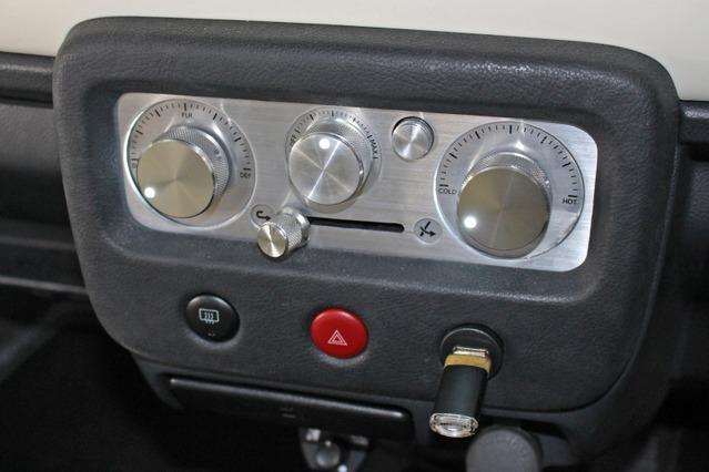 エアコンパネルはアルミを使ったワンオフ処理とした。AV用のノブを使った操作部もクラシカルなムードを引き出す。