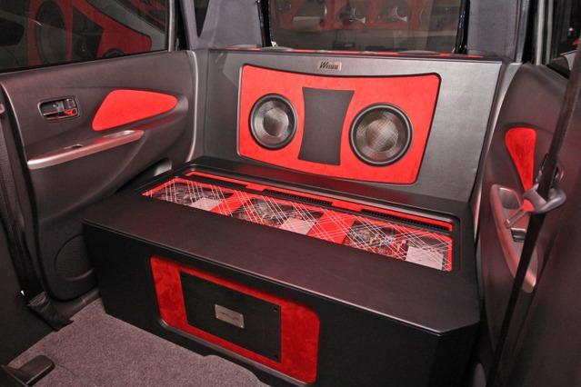 リアシートのスペースを丸ごと使ったアンプラック&ウーファーボックス。ブラックとレッドのコントラストが鮮烈だ。