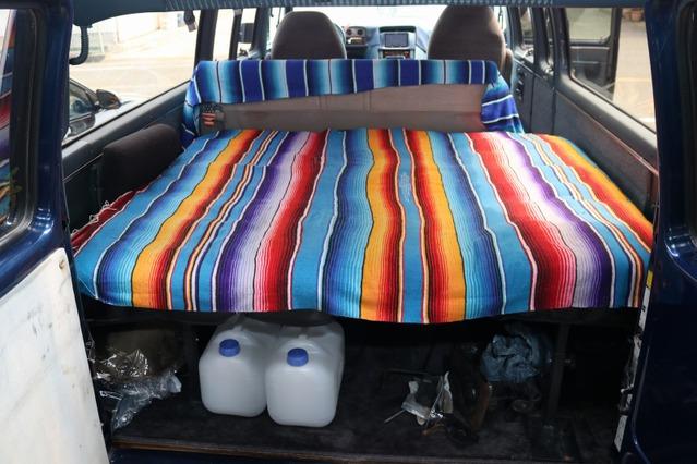 ラゲッジスペースにはベッドキットを装着。ハイエース用のパーツを横向けに設置してピタリとフィットさせたのはアイデア。