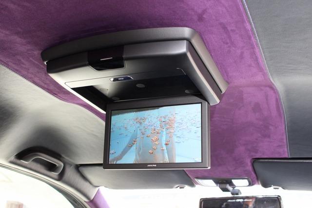 家族や仲間とのドライブに備えて後席にはフリップダウンモニターを設置。天井の張り替え処理も美しい仕上がりだ。