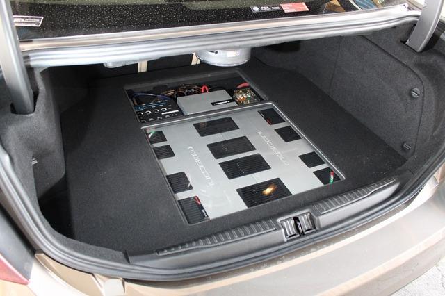 モスコニのアンプをトランクルームのフロアに敷き詰めるデザインを実施。フロアは一段かさ上げされ床下にユニットを収めた。