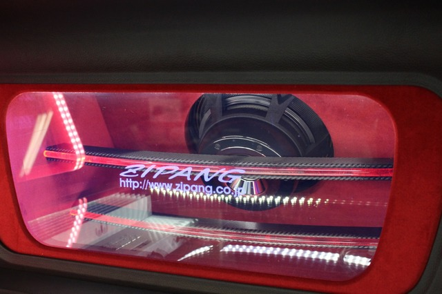 トランクルーム前方のウォールには後面をアクリル処理したエンクロージャーを設置。TS-W1000RSのマグネット面を見せる。